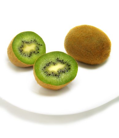 A group of cut and whole kiwis on white plate and isolated on white background