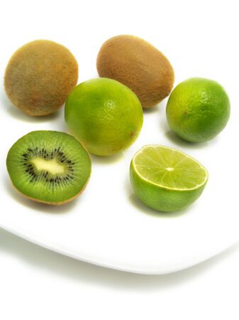 A group of fresh kiwis and limes on a white plate and isolated on white background Stock Photo - 3317649