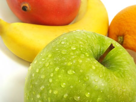 A fresh green apple with water drops and in the background a blurred mango, banana and orange Stock Photo - 3332113