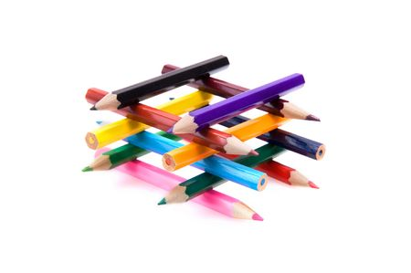 Closeup of a collection of bright color pencils forming a building. Isolated on white.