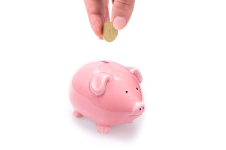 Closeup of a hand putting a coin in a pink piggy bank. Isolated on white.