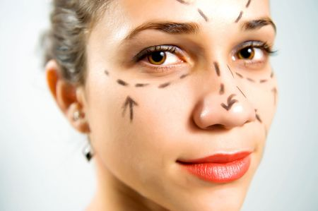 Closeup portrait of a pretty Caucasian womans face marked with lines for facial cosmetic surgery
