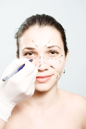 Drawing lines on an attractive Caucasian ladys face as marks for facial plastic surgery Stock Photo