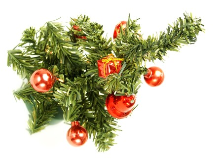 Closeup photo of a nice artificial Christmas tree decorated with red baubles, present boxes, bells. Isolated on white.