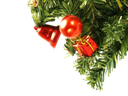 Closeup photo of a nice red Christmas decoration bauble, present box, bell hanging on artificial Christmas tree branch. Isolated on white.