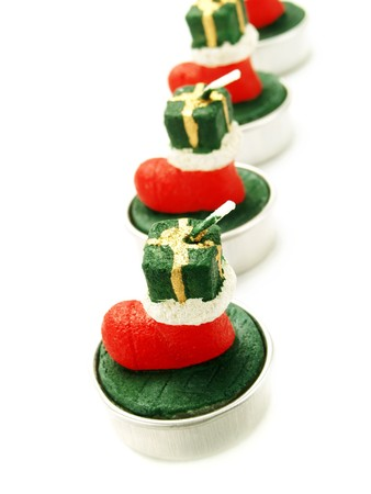 Closeup photo of a line of nice Christmas decoration green candles with red boots on them. Isolated on white.