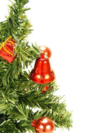 Closeup photo of a nice artificial Christmas tree decorated with red Christmas ornaments: baubles, present boxes, bells. Isolated on white.