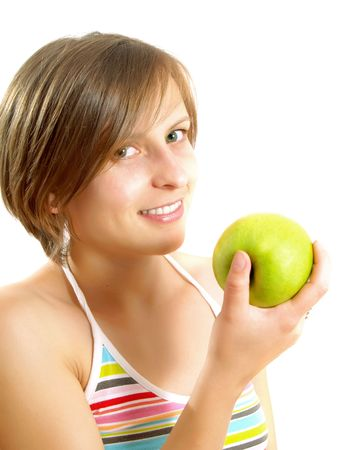 Portrait of a pretty Caucasian blond girl with a nice colorful striped dress who is smiling and she is holding a green apple in her hand. Isolated on white. photo
