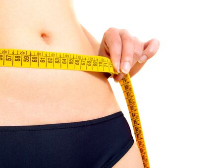 Closeup photo of a Caucasian womans abdomen and breasts. She is measuring her waist with a yellow metric tape measure after a diet. photo