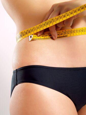 cinta de medir: Closeup foto de una mujer de raza cauc�sica del abdomen. Ella es la medici�n de la cintura con una cinta m�trica amarilla despu�s de una medida de la dieta. Foto de archivo