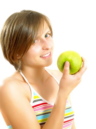 Portrait of a young pretty Caucasian blond woman with a nice colorful striped dress who is smiling and she is holding a green apple in her hand. Isolated on white. Stock Photo