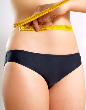 Closeup photo of a Caucasian womans abdomen. She is measuring her waist with a yellow metric tape measure after a diet. photo