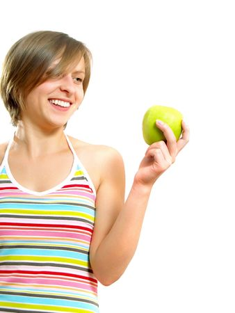 Portrait of a pretty Caucasian blond lady with a nice colorful striped dress who is smiling and she is holding a green apple in her hand. Isolated on white. Stock Photo