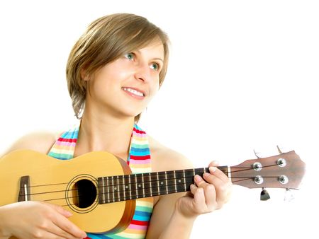 Portrait of a cute Caucasian blond girl with a nice colorful striped summer dress who is smiling and she is playing an ukulele (small Hawaiian guitar). Isolated on white.