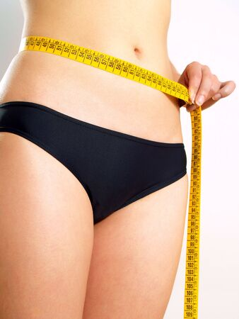 Closeup photo of a Caucasian womans abdomen. She is measuring her waist with a yellow metric tape measure after a diet.