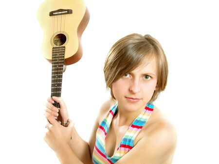 Portrait of a cute Caucasian blond girl with a nice colorful striped summer dress who is angry and she want to fight with an ukulele (small Hawaiian guitar). Isolated on white.