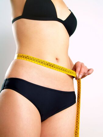 Closeup photo of a Caucasian womans abdomen and s. She is measuring her waist with a yellow metric tape measure after a diet. photo