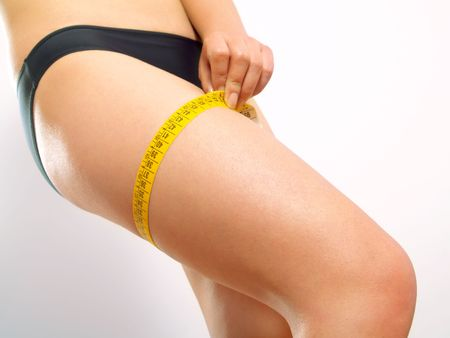 Closeup photo of a Caucasian womans leg. She is measuring her thigh with a yellow metric tape measure after a diet. photo