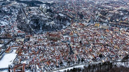 Brasov, Transylvania. Romania. Panoramic view of the old town and Council Square, Aerial twilight of the city covered with snow.
