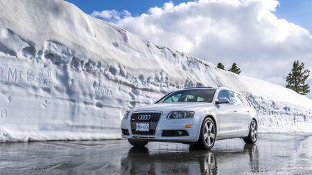 Washington, Estados Unidos. Mount Baker. 10 de mayo de 2019. Un coche junto a un enorme muro de nieve. Audi A6 Quattro, carretera en nieve profunda del invierno.