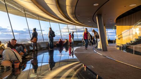 SEATTLE, WASHINGTON, USA. June 19, 2019 Residents and tourists inside the Space Needle to catch a spring sunset over downtown Seattle and Mt. Rainier seen in the distance.