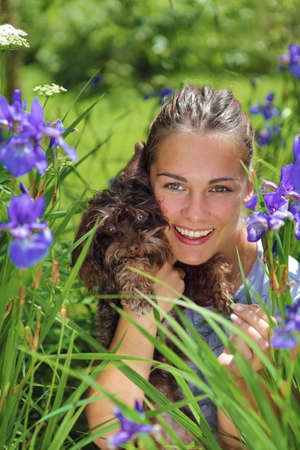 Portrait of a girl with dog surrounded with blue flowers photo