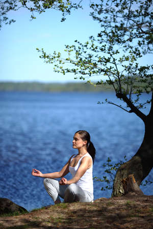 young girl training yoga near a lake under a tree