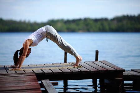 young girl training yoga near a lake Stock Photo - 9597525