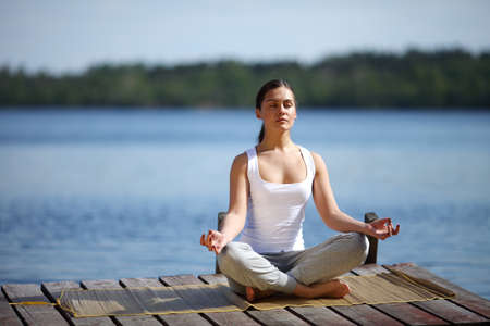 young girl training yoga near a lake Stock Photo - 9597610