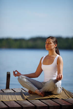 young girl training yoga near a lake Stock Photo - 9597478