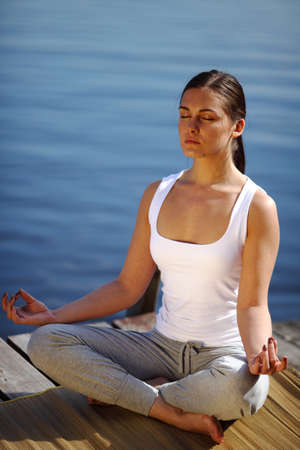 young girl training yoga near a lake