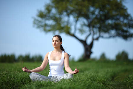 young girl training yoga on sunny meadow