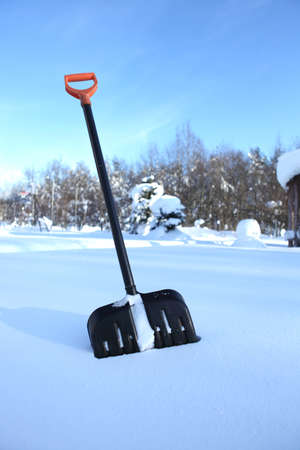 Black snow shovel with yellow handle stick in snow Stock Photo - 11293858