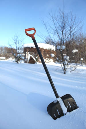 Black snow shovel with yellow handle stick in snow Stock Photo - 11293862