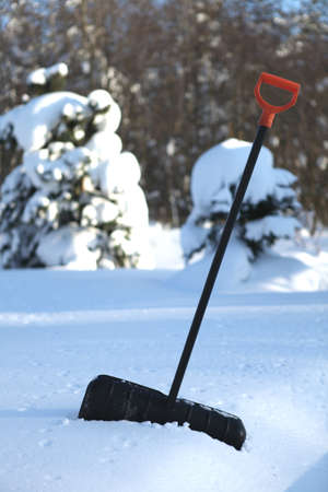 Black snow shovel with yellow handle stick in snow photo