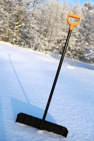 Black snow shovel with yellow handle stick in snow Stock Photo - 11293867