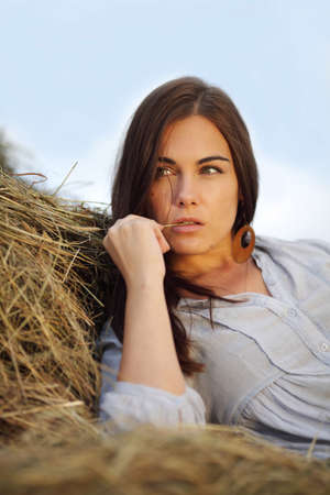 beautiful girl on stack of hay photo