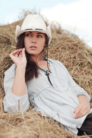 country girls: beautiful girl on stack of hay Stock Photo