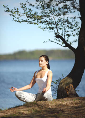woman meditation: beautiful young girl training yoga near a lake under a tree