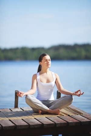 beautiful young girl training yoga near a lake photo