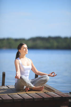 beautiful young girl training yoga near a lake photo