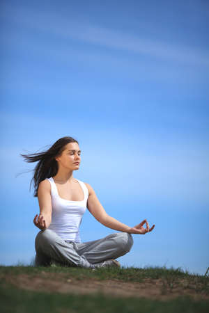 beautiful young girl training yoga on sunny meadow photo