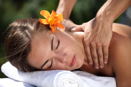 woman lying down: Young woman lying on massage table at spa, outdoors Stock Photo