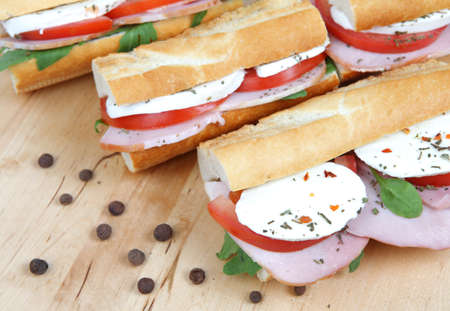 three fresh sandwiches with tomato , ham and mozzarella photo