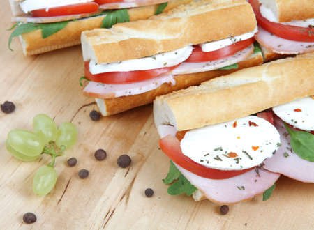 Closeup of three fresh sandwiches with tomato , ham and mozzarella photo