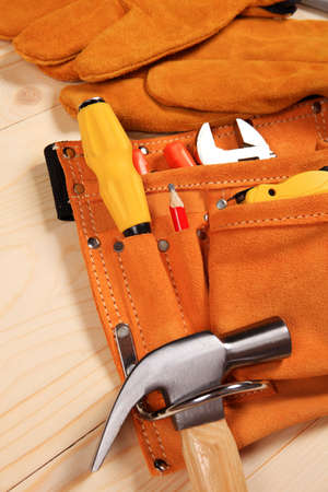 carpenter vise: Hammer, pliers, red pencil, work gloves and other tools isolated on a wooden background