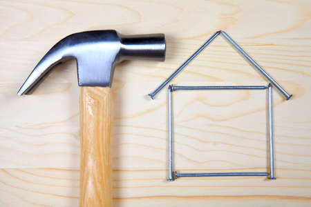 hammer head: Head of hammer and house from nails on wooden background Stock Photo