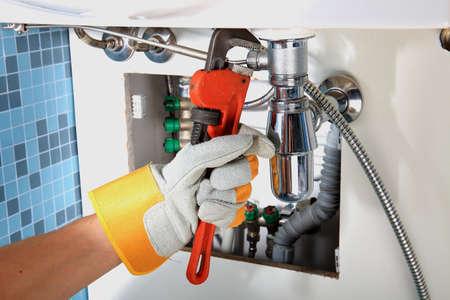 Plumbing work and sanitary engineering repairing a pipe under a sink. Sanitary works. Plumber repairing 스톡 콘텐츠