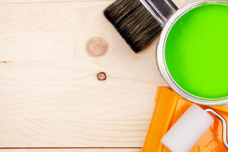 paintroller: Colorful bucket of green paint on a table. Paintroller in tray with paint can on a wooden background Stock Photo