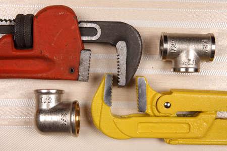 fontaneria: Conjunto de plomería y herramientas sobre la mesa. Montaje, guantes de gamuza gris y dos llaves ajustables para trabajos de plomería